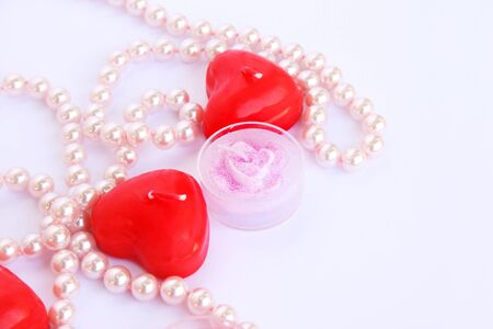 Heart shape red candles and necklace isolated on grey background. photo