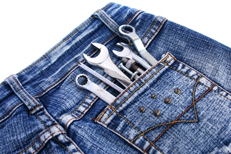 Tools in blue jeans pocket on white background. photo