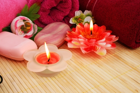 Towels, soaps, flowers and candles on mat background. photo