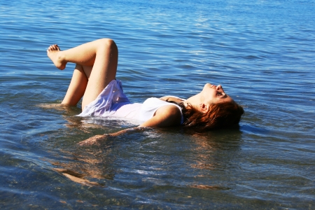 Pretty woman lying in the sea  photo