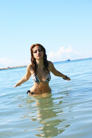 Pretty woman in swimwear standing in sea. photo