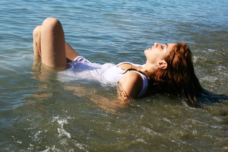Pretty woman lying in the sea. photo