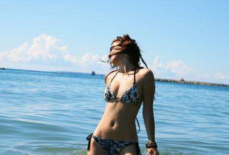 Pretty woman in swimwear standing in sea. Stock Photo - 17279322