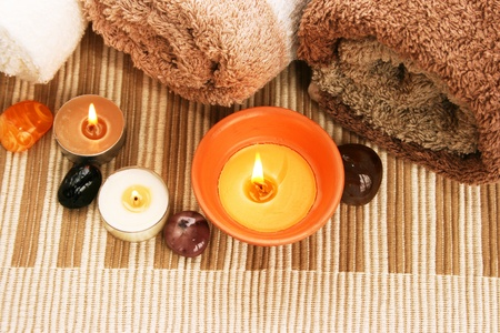 Towels, candles, stones on mat background.