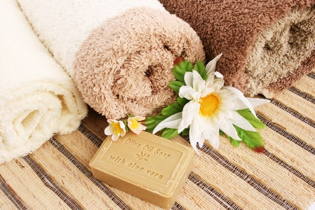 aloe vera flowers: Towels and olive oil soap with aloe vera, flowers on mat background..