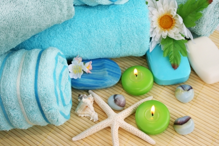 Stack of towels, soaps, candles, stones, flowers on mat background. photo