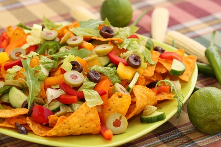 Heap of nachos with vegetables on green plate.