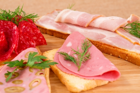 Sandwiches with salami, bacon and mortadella on wooden board. photo