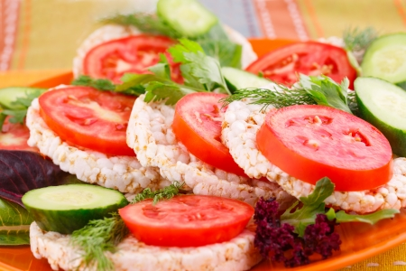 Puffed rice crackers sandwiches with vegetables on plate. photo