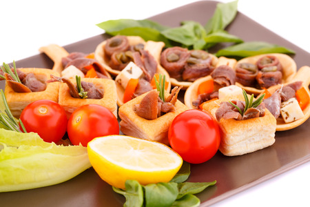 Anchovies in pastries, lemon, tomato, lettuce and basil on brown plate. photo