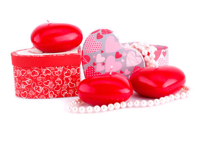 bijoux: Red heart candles, necklaces and gift boxes on white background. Stock Photo