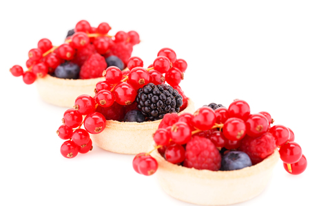 Fresh ripe berries in tartlets isolated on white background. photo