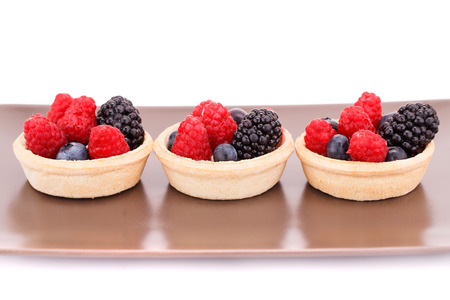 Fresh ripe berries in tartlets on brown plate. photo