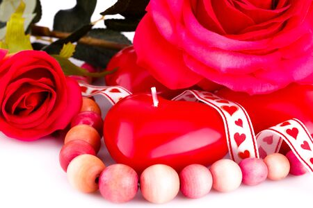 Red heart candles, wooden necklace, ribbon and roses on white background. photo