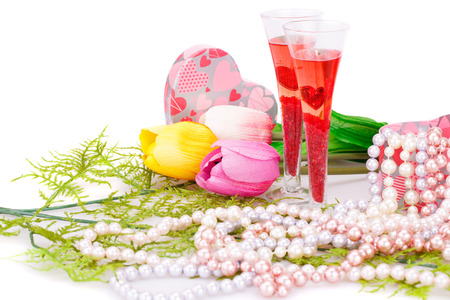 Two glasses, flowers, colorful pearls necklaces and gift box on white background. photo