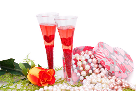 Two glasses, rose, colorful pearls necklaces and gift box on white background. photo