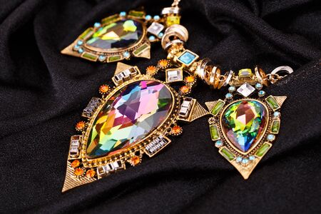 edelstenen: Stylish necklace with gemstones on fabric background.