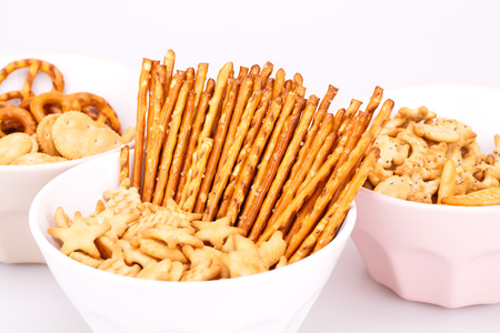 pretzel stick: Different salted crackers in bowls on white background.