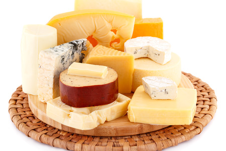 Various type of cheese on wooden board closeup picture.