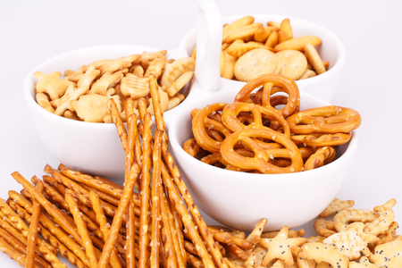 pretzel stick: Different salted crackers in bowl on white background. Stock Photo