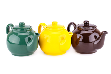 Green, yellow and brown teapots isolated on a white background. Stock Photo