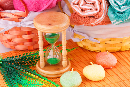 Spa set with colorful towels, candles and sandglass on bamboo background.