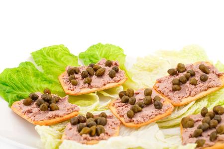 plato del buen comer: Paté de carne con alcaparras en galletas y lechuga en un plato. Foto de archivo