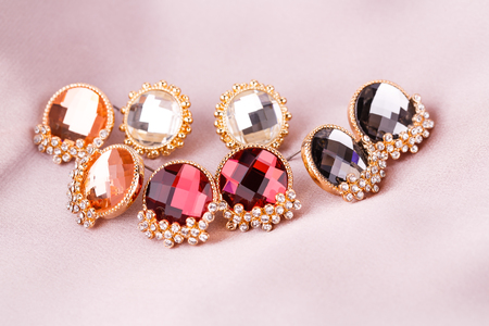 personal ornaments: Stylish earrings with stones on fabric background.
