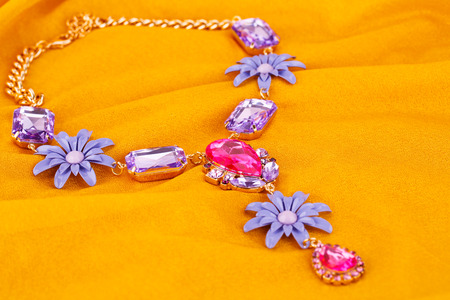 personal ornaments: Stylish necklace with colorful stones on yellow fabric background.