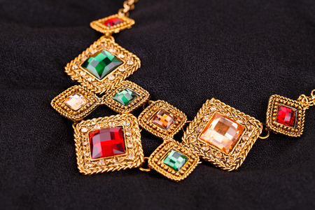 personal ornaments: Stylish necklace with colorful stones on black fabric background.