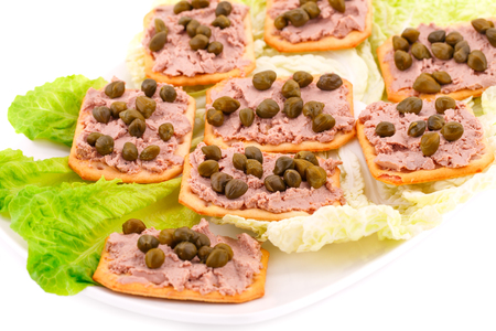 alcaparras: Meat pate with capers on crackers and lettuce on plate.