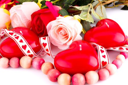 bijoux: Red heart candles, wooden necklace, ribbon and roses on white background.