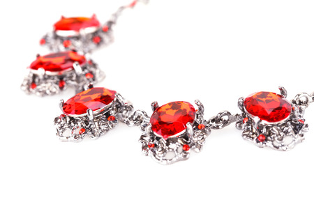 personal ornaments: Stylish necklace with red stones isolated on a white background.