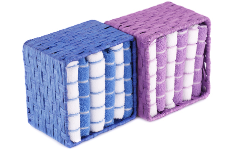 Pink, blue and white folded towels in boxes isolated on white background. Stock Photo