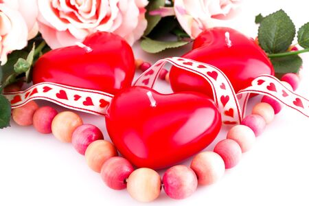 bijoux: Red heart candles, wooden necklace and ribbon on white background.