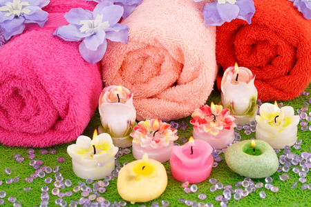 Spa set with towels, candles and flowers on plastic background.