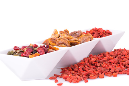 chinese wolfberry: Dried fruits, berries and seeds in bowl on white background. Stock Photo