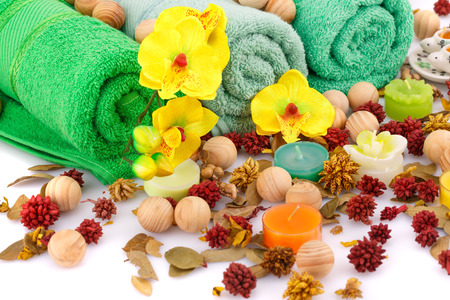 absorbent: Spa set with towels, candles, wooden balls and flowers closeup picture.