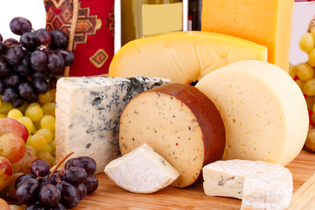Various type of cheese, wines and grapes on wooden board closeup picture.