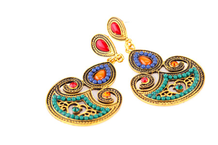 personal ornaments: Ancient style earrings with colorful stones isolated on white background.