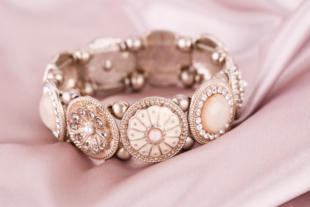 personal ornaments: Stylish bracelet with stones on fabric background.