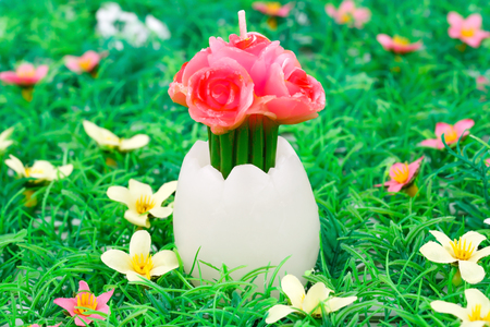 easter candle: Easter egg with flower candle on articial grass background.