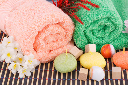 absorbent: Colorful rolled towels with flowers, candles and stones closeup picture. Stock Photo