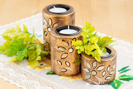 old desk: Three brown ancient style candle nests and green leaves on cloth background.