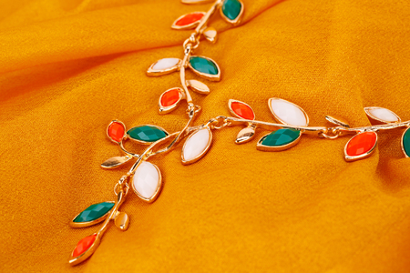 Stylish necklace with colorful stones on yellow fabric background.