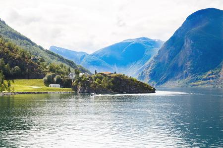 Paysage avec Naeroyfjord, montagnes et maisons de village traditionnelles en Norvège.