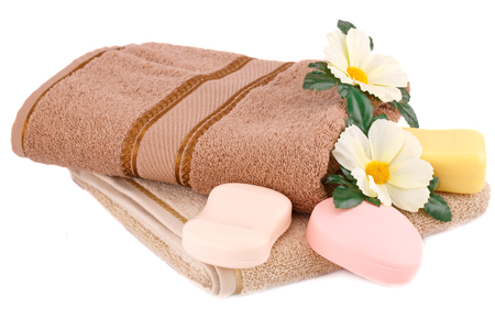 Folded towel, soaps and flowers isolated on white background. Stock Photo