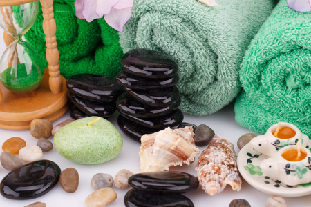 Spa set with towels, candles, shells, sandglass and stones closeup picture. Stock Photo