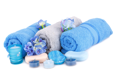 Spa set with towels, candles, flowers and various soaps isolated on white background.