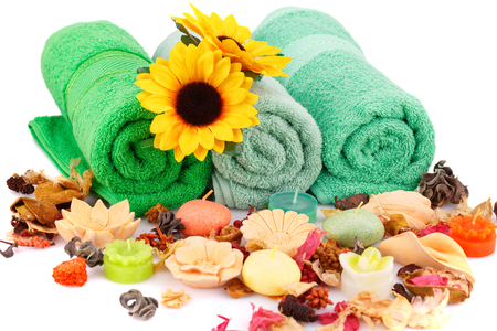 Spa set with towels, candles, flowers and various formed soaps closeup picture.